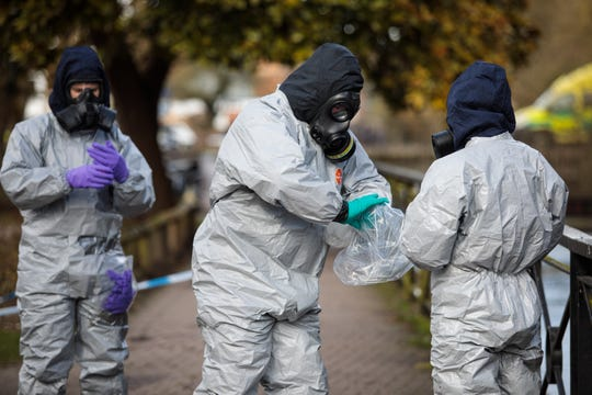 Police officers in protective suits and masks work near the scene where former double-agent Sergei Skripal and his daughter, Yulia, were discovered after being attacked with a nerve-agent on March 16, 2018, in Salisbury, England.