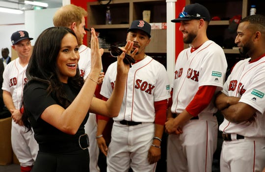 Prince Harry and Meghan meet with Red Sox players in the clubhouse.