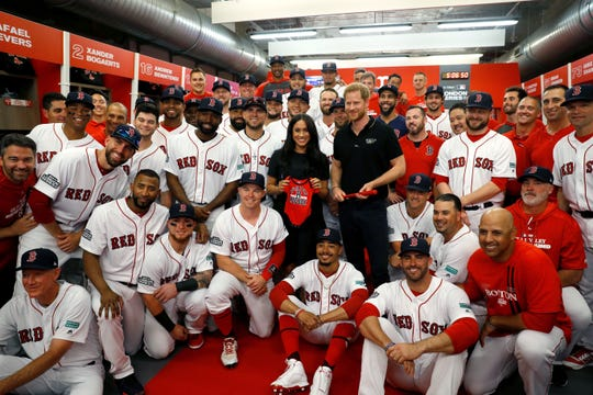Prince Harry and Meghan pose with Red Sox players in the clubhouse at London Stadium.