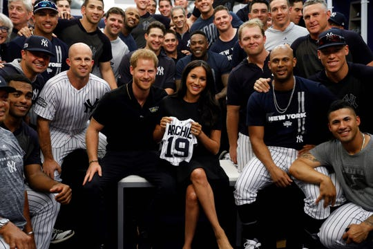 Prince Harry and Meghan pose with the baby gift given to them by the Yankees.