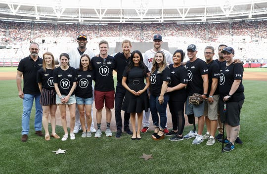 Harry and Meghan pose with Yankees pitcher CC Sabathia, Red Sox pitcher Chris Sale and members of the Invictcus Games foundation at London Stadium.