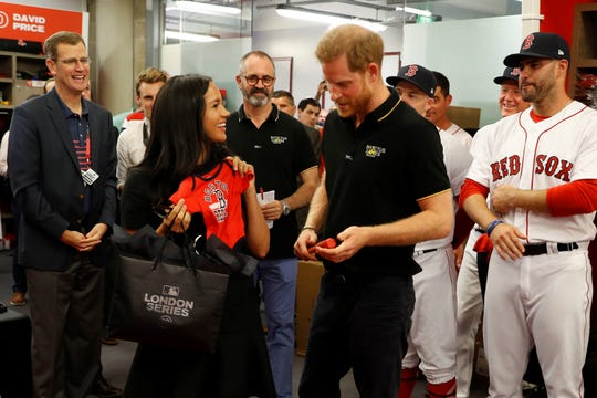 Meghan and Prince Harry with a baby gift given to them by the Red Sox.