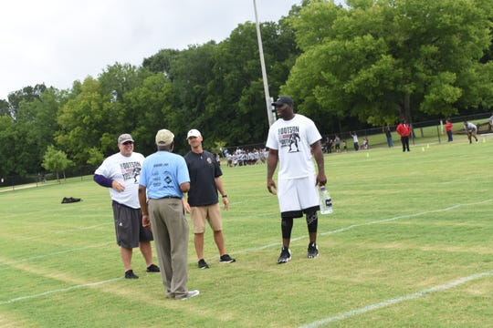 Demar Dotson (right), an offensive lineman for the Tampa Bay Buccaneers and a former Alexandria Senior High School football player, talks to current ASH coach Thomas Bachman (center) and assistant Dwayne Severio (left), during his football camp at Frank O. Hunter Park Saturday, June 29, 2019. This is the fifth year Dotson has held the free camp for area youth which he wants to inspire and teach them proper skills and techniques.