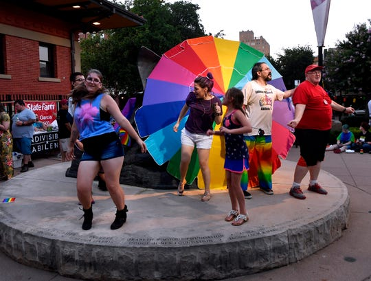 Attendees of the Pride in the Park gathering dance to recorded music in front of a rainbow-colored umbrella in Everman Park Saturday.