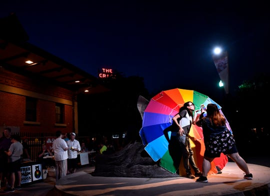A couple use a rainbow-colored umbrella as a backdrop for taking photographs during Saturday's Pride in the Park gathering.