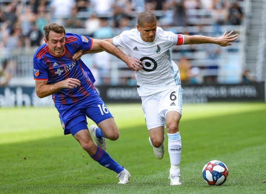 Jun3 29, 2019: FC Cincinnati midfielder Eric Alexander (16) and Minnesota United midfielder Osvaldo Alonso (6) battle for the ball during the first half at Allianz Field in St. Paul, Minnesota.