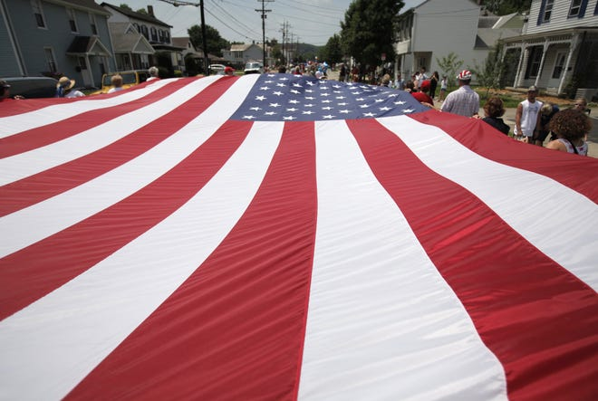 July 3, 2011: The Harrison Historical Society had fun carrying the 20-by-30 American flag during the Annual Harrison Fourth of July Celebration.