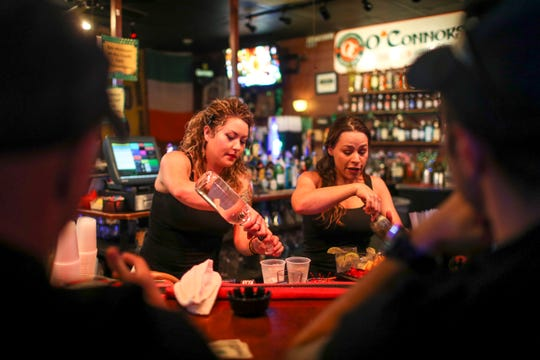 Bartenders Megan Haar and Casey Adams put together drinks at their station at O'Connors Irish Pub and Grill in Clarksville, Tenn., on Friday, June 28, 2019.