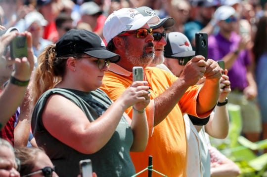 Spectators take photos during the final round of the Rocket Mortgage Classic at the Detroit Golf Club in Detroit on Sunday, June 30, 2019.