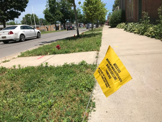 A Miss Dig warning flag — yellow for natural gas — marks a buried pipe under a sidewalk on Mack Avenue in Grosse Pointe Farms on Sunday.