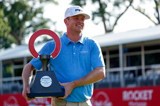Nate Lashley holds the Rocket Mortgage Classic trophy as he poses for photos after winning the tournament at the Detroit Golf Club in Detroit on Sunday, June 30, 2019.