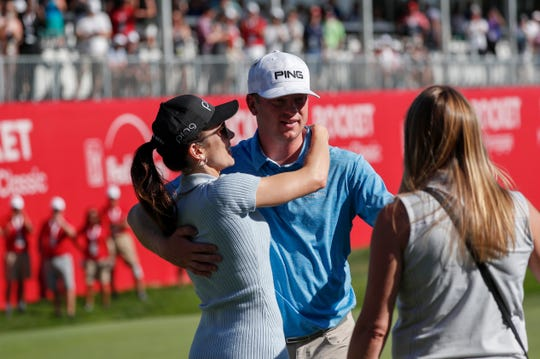 Ashlie Reed hugs boyfriend Nate Lashley as he reaches out toward his sister Brooke Lashley after winning the Rocket Mortgage Classic at the Detroit Golf Club on Sunday.