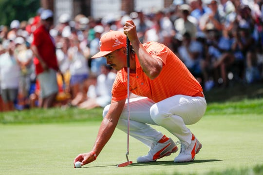 Rickie Fowler lines up his ball on the green during the final round of the Rocket Mortgage Classic at the Detroit Golf Club in Detroit on Sunday, June 30, 2019.