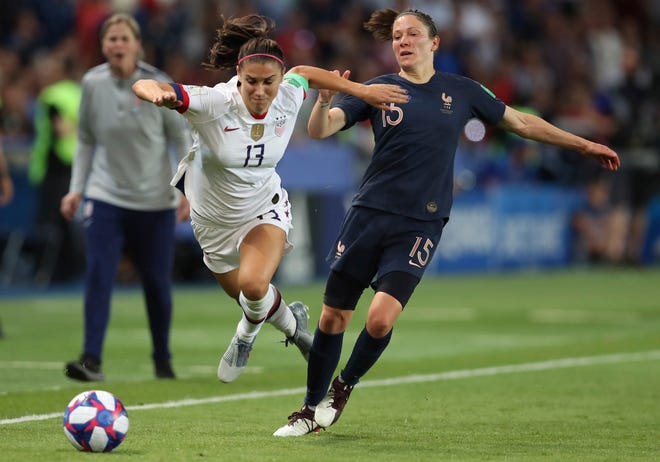 United States' Alex Morgan, left, competes for the ball against France's Elise Bussaglia during the World Cup quarterfinal match.