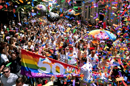 New York Gov. Andrew Cuomo, lower front center, joins people participating in the LBGTQ Pride march Sunday in New York.