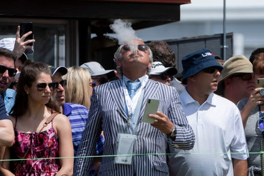 Joseph Saker, of Birmingham, enjoys a cigar at the third tee during the final round of the Rocket Mortgage Classic Sunday.