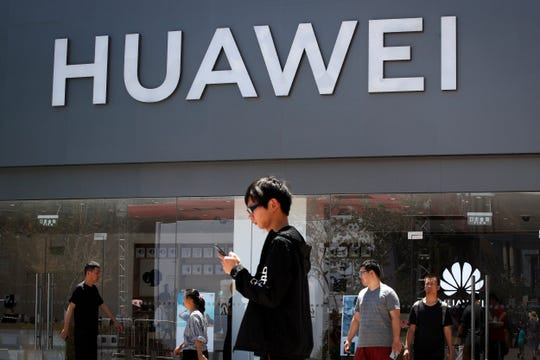 People walk past a Huawei retail store in Beijing, Sunday, June 30, 2019. Once again, Presidents Donald Trump and Xi Jinping have hit the reset button in trade talks between the world's two biggest economies.