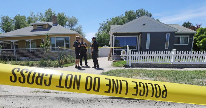 Police officers stand in front of the home, right, of Ayoola A. Ajayi Friday, June 28, 2019, in Salt Lake City.