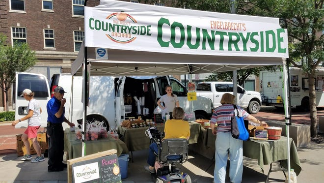 In summer of 2019, local peaches were drawing a crowd at Engelbrecht's Countryside Orchard stand at the Wednesday downtown Market on Main.