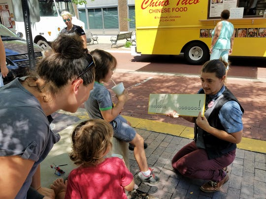 Zack Hoskins of Evanville Vanderburgh Public Library reading to kids at at the Wednesday downtown Market on Main.