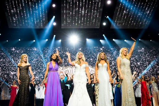 The top five contestants smile from the stage  during the final round of the Miss Tennessee Scholarship Competition on June 29. From left, they are Miss Middle Tennessee Savannah Maddison, Miss Greene County Brianna Mason, Miss West Tennessee Abbie Bayless, Miss Lexington Lauren Dickson and Miss Music Row Tally Bevis.