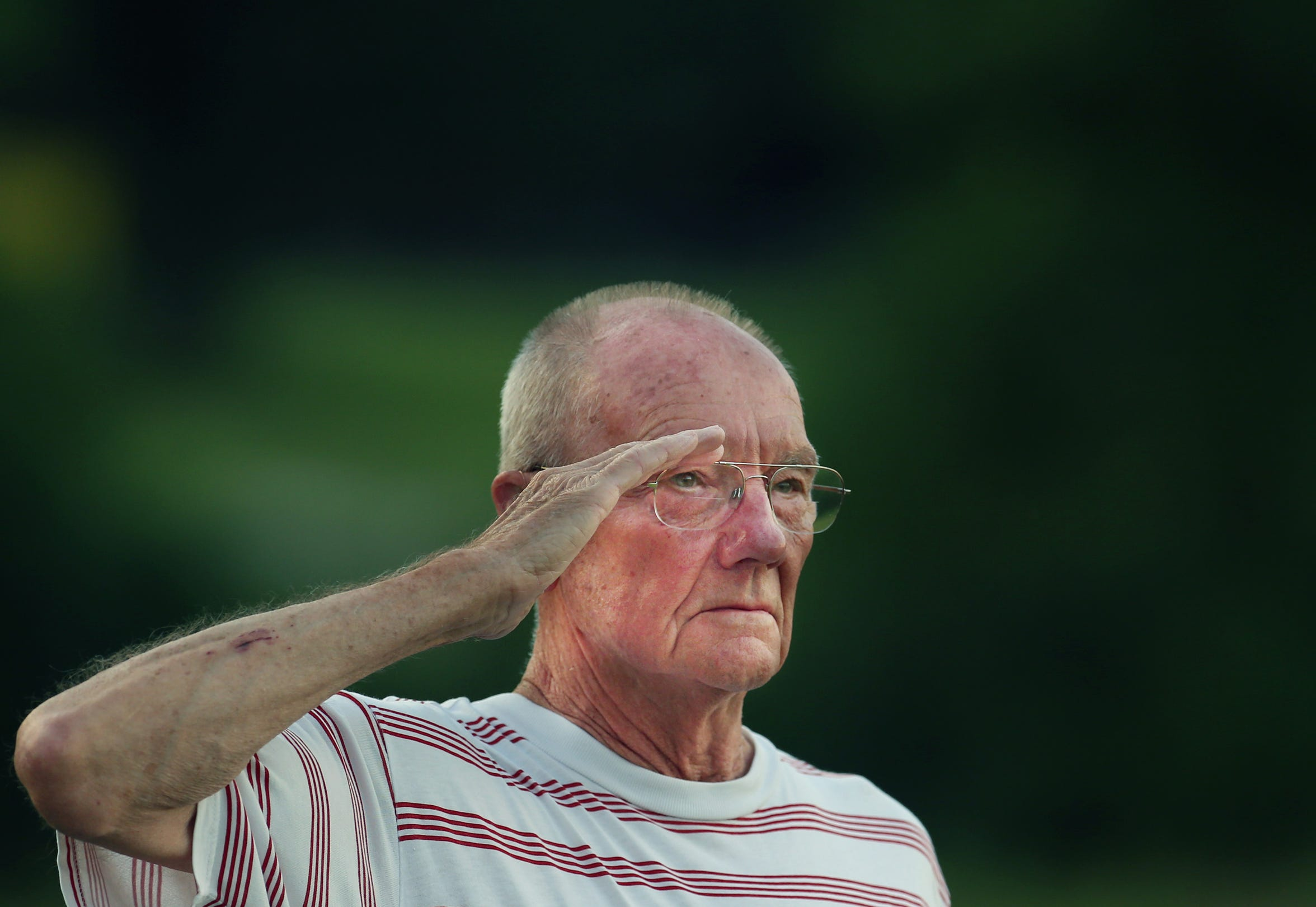 Ray Wolken, who joined the U.S. Army 64 years ago, salutes during a flag retirement ceremony by the Jeffersontown American Legion G.I. Post 244. Tens of thousands of American flags are under the large flag retired from Town & Country Ford. John Wright, with the post, believes that this flag retirement ceremony might be the largest in the U.S. June 29, 2019.