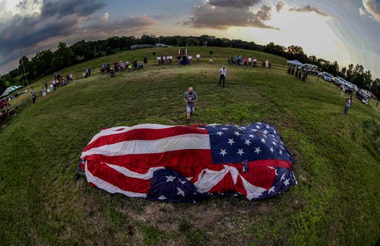 "Morgan Colbert brings one last American flag to a large stack during a flag retirement ceremony by the American Legion ""G.I. Joe"" Post 244 on June 29 in  Jeffersontown, Ky."