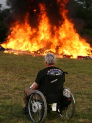 Jim Walser pays respect to his father, uncle and the thousands of American flags as they burn during a flag retirement ceremony on June 29, 2019.