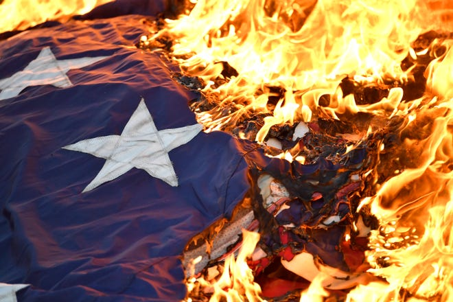 Flames consume a stack of United States flags numbering in the thousands as they are burned in a flag retirement ceremony, Saturday, Jun. 29, 2019 in Shelby County Ky.