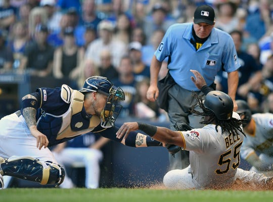 Josh Bell is tagged out at home by Brewers catcher Yasmani Grandal as the Pirates slugger was trying to score from first on a ball hit off the right-field wall in the first inning.