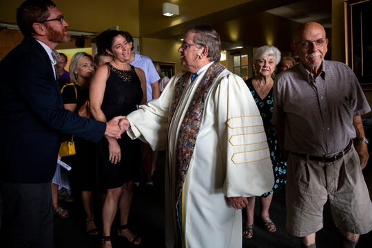 Well wishers shake hands and speak with retiring Pastor Ted Sauter after his final Sunday service at North Naples Church on June 30, 2019.