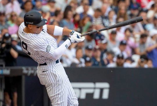 New York Yankees right fielder Aaron Judge (99) hits a single in during the fourth innings of the game between the Boston Red Sox and the New York Yankees at London Stadium.