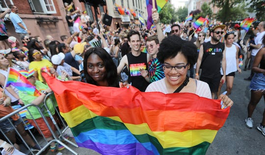 Summer Galarda 18 and Ishana Grant 17 hold the rainbow flag as they walk, just past The Stonewall Inn.  Sunday June 30, 2019