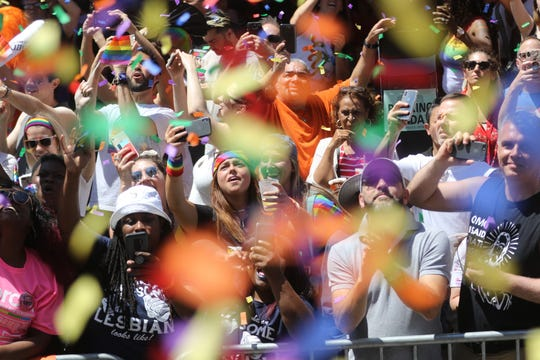 People cheer for the Pride March as rainbow confetti rains down on them on 7th Ave. Sunday June 30, 2019