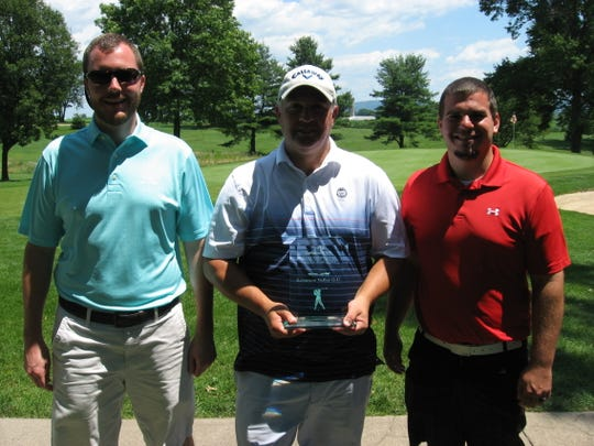 Jim Gardner is presented the championship trophy for winning the Lebanon County Amateur by tournament directors Justin Arnt, left, and Jon Day.