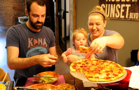 Sam Richins eats a pizza with his wife Jenelle Richins and his daughter Sophia, 1, at the new Original Pizza Cookery at the Best Western hotel in Thousand Oaks.