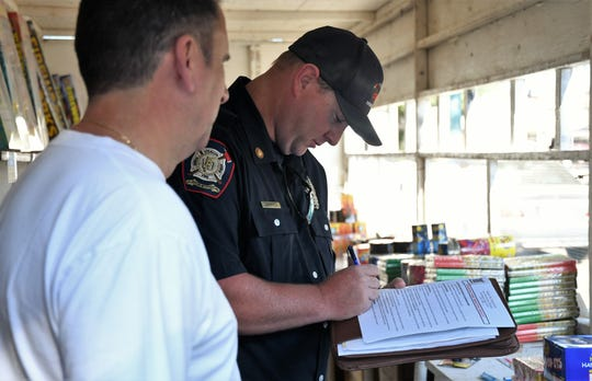 Visalia Fire Marshal Corbin Reed inspects a fireworks booth on Caldwell Avenue and Court Street on Saturday, June 29, 2019.