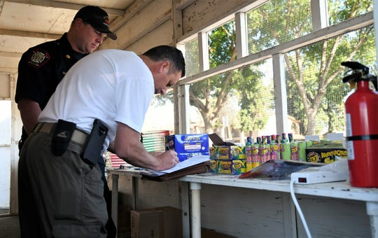James Wilfong signs inspection paperwork to start selling fireworks at the Knights of Columbus booth located at Caldwell Avenue and Court Street.
