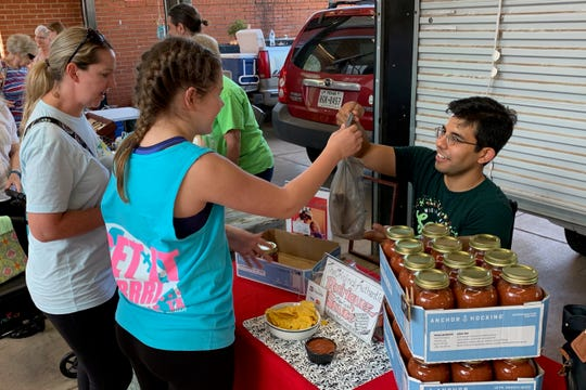 "Joey Diaz sells salsa last Saturday at the Farmers Market. The salsa is made from the same recipe his grandmother  made and sold at the flea market, ""The Original Authentic Rodriguez Mexican Sauce."""