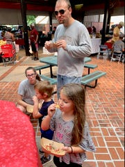 Zach Skelton, his wife Anne and children Claire and Leo enjoy the black eyes peas dish samples last Saturday at the Farmers Market on Black Eyed Pea day.
