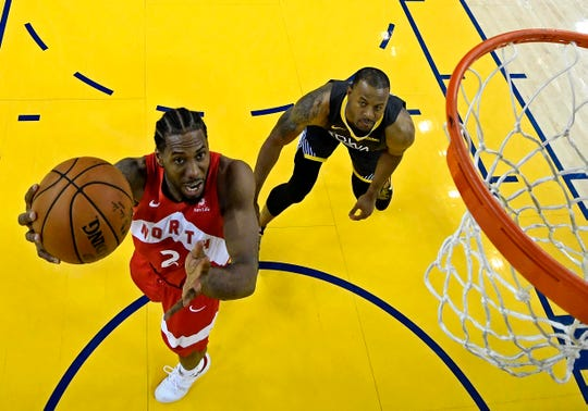 Raptors forward Kawhi Leonard (2) shoots the ball in opposition to Warriors guard Andre Iguodala (9) in Sport 6 of the NBA Finals.