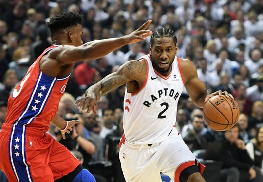 Toronto Raptors forward Kawhi Leonard dribbles the ball against Philadelphia 76ers guard Jimmy Butler.