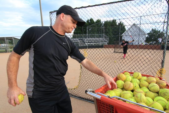 Coach Jeff Craft grabs a softball during a Dixie East softball team batting practice drill at Crescent High School in Iva.