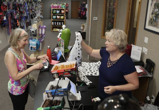Laurie Koestner, owner of pet supply store DePawsitory, helps customer Barb Akgulian on June 28, 2019, in downtown Appleton.