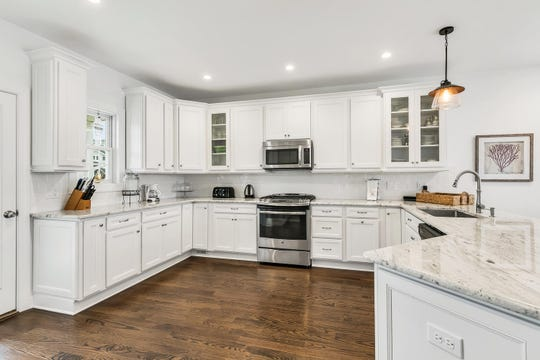 The kitchen features granite stone counters with custom white cabinetry.