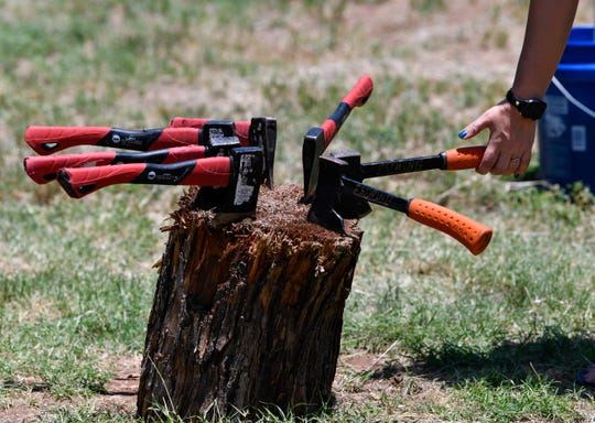 Axes rest on a stump as a customer lifts one to throw Saturday at Sockdolager Brewing Company.