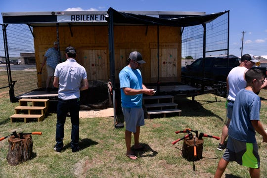 Participants and owners of Abilene Axe Company wait stand beside the custom trailer Saturda. Built like a cage, the sides open into two alleys for two sets of dueling competitors to throw axs at wooden targets.