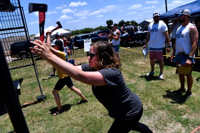 Kristi Brokaw (center) competes with her friend Emily Savage throwing axes Saturday at Sockdolager Brewing Company. Abilene Axe Company is a new business, opening in April.