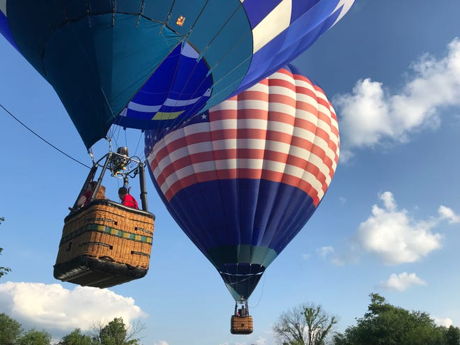 Phil Clinger, left, and Chad Crabtree of Delton, launch their balloons for an evening flight in June. Clinger is the event director for the first time at Field of Flight and Crabtree is competing for the first time.