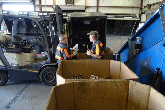 Steve Cazzell, left, and Randy Burton sort items from a recycling trailer Thursday at the Crawford County Recycling Center.